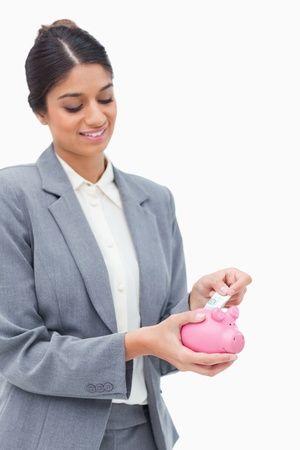 Smiling bank assistant putting bank note into piggy bank against a white background photo