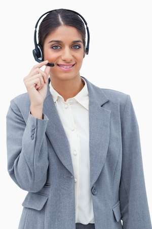 Smiling call center agent adjusting microphone against a white background Stock Photo - 13600344