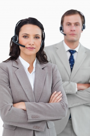 Call center agents with headsets and arms folded against a white background photo