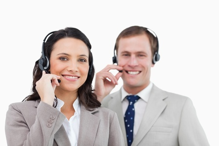 Smiling call center team with their headsets against a white background Stock Photo - 13606471