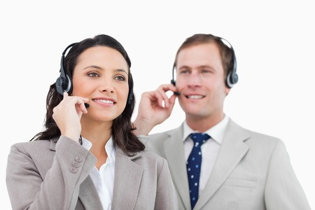 Telephone help desk employees with headsets against a white background Stock Photo - 13606588