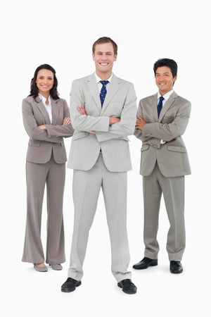 Smiling businessteam with folded arms against a white background photo