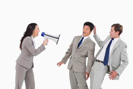Businesswoman with megaphone yelling at colleagues against a white background photo