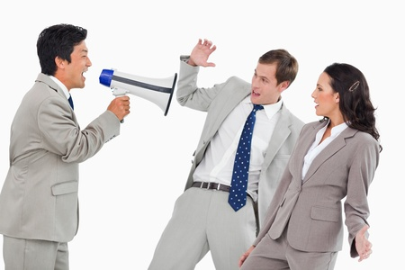 Businessman with megaphone yelling at colleagues against a white background photo