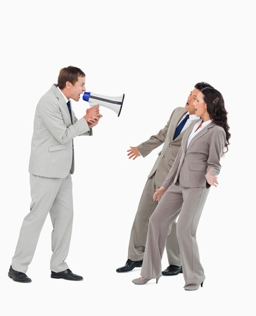 Businessman with megaphone yelling at associates against a white background Stock Photo - 13601814