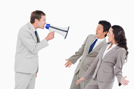 Salesman with megaphone shouting at associates against a white background photo