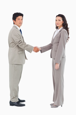 Side view of trading partners shaking hands against a white background photo