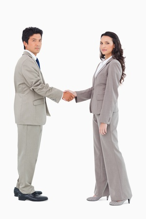Side view of businesspeople shaking hands against a white background photo