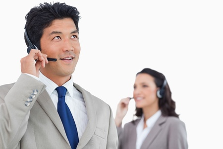 Call center agent with headset and colleague behind him against a white background photo
