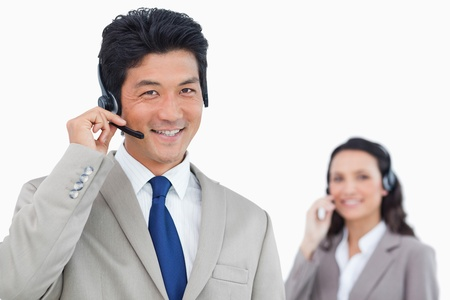 Smiling call center agent with colleague behind him against a white background Stock Photo - 13609676