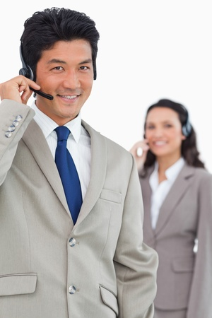 Smiling customer support employee with colleague behind him against a white background photo