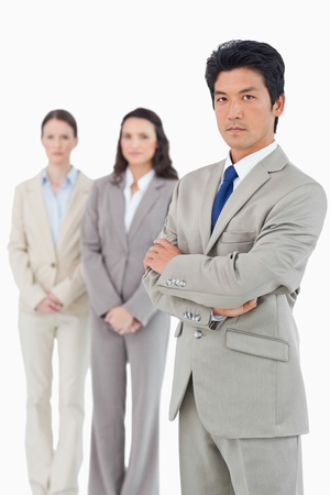 Confident looking businessman with his team behind him against a white background photo