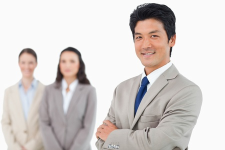 Confident smiling businessman with his team behind him against a white background Stock Photo - 13606489