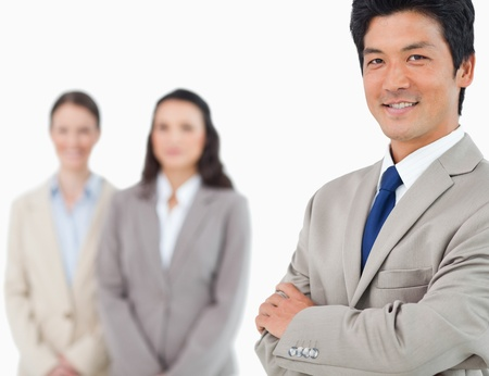 Smiling young businessman with colleagues behind him against a white background Stock Photo - 13605951