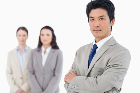 Confident businessman with employees behind him against a white background photo