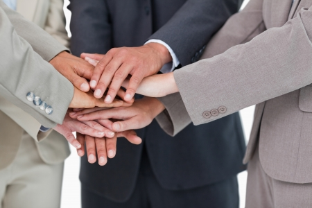 Hands of businesspeople together against a white background photo