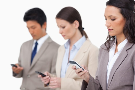 Businessteam looking at their cellphones against a white background Stock Photo - 13615808
