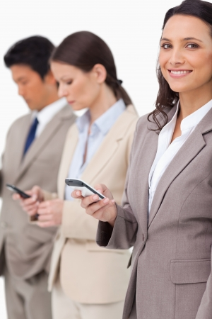Smiling businesswoman with cellphone next to colleagues against a white background photo