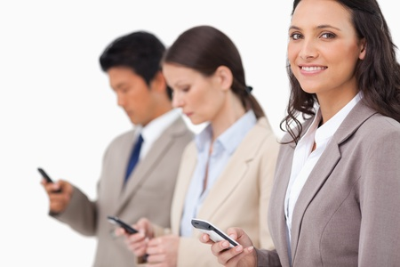 Smiling saleswoman with cellphone next to colleagues against a white background photo