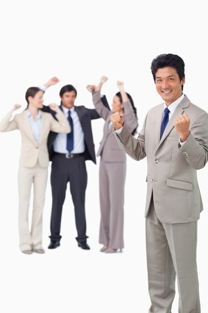 Successful businessman with cheering team against a white background photo