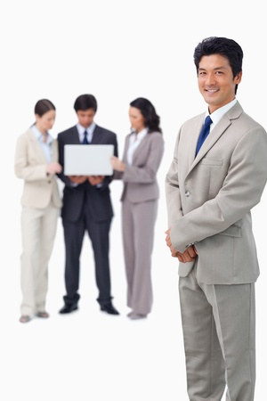 Salesman with colleagues and laptop behind him against a white background photo