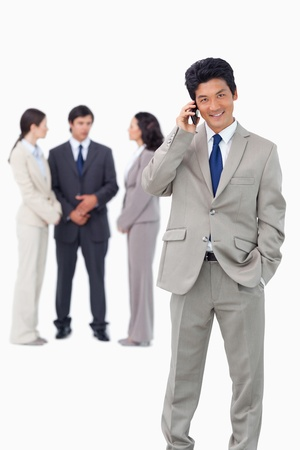 Businessman on cellphone with team behind him against a white background Stock Photo - 13607084