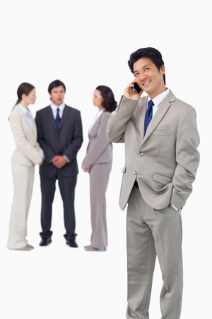 Businessman with cellphone and colleagues behind him against a white background photo