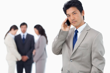 Serious businessman on cellphone with team behind him against a white background Stock Photo - 13615434