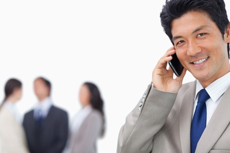 Smiling businessman on mobile phone and team behind him against a white background photo