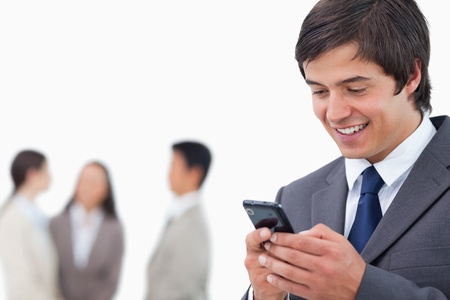 Salesman writing text message with team behind him against a white background Stock Photo - 13609408