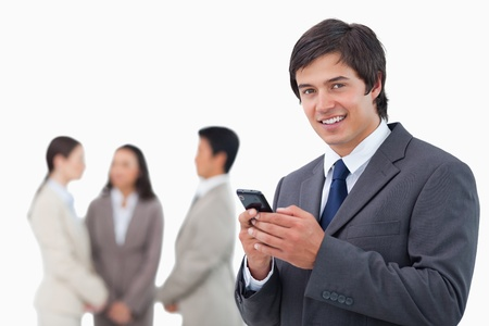 Salesman holding cellphone with team behind him against a white background photo