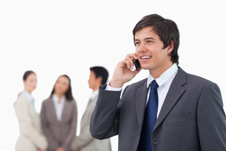 Salesman talking on cellphone with colleagues behind him against a white background photo