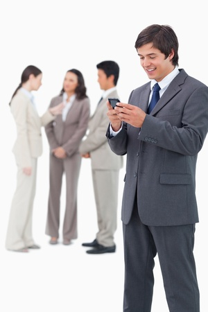 Smiling salesman holding mobile phone with team behind him against a white background photo