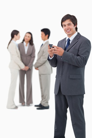 Smiling tradesman with cellphone and colleagues behind him against a white background photo