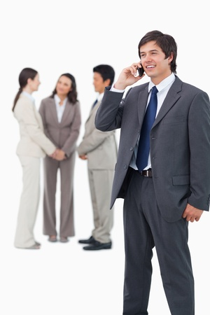 Smiling tradesman on cellphone with team behind him against a white background Stock Photo - 13609426