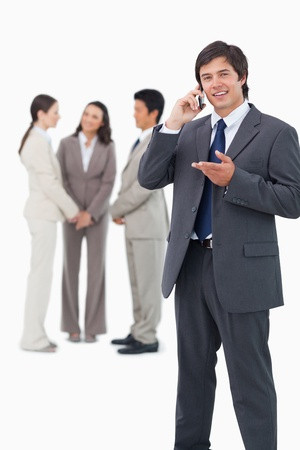Salesman talking on cellphone with team behind him against a white background photo