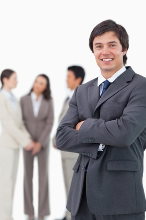 Smiling salesman with arms crossed and team behind him against a white background photo