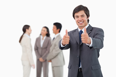 Salesman giving his approval with team behind him against a white background photo