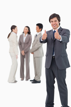 Salesman giving thumbs up with colleagues behind him against a white background photo