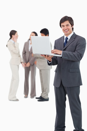 Smiling salesman with laptop and team behind him against a white background photo