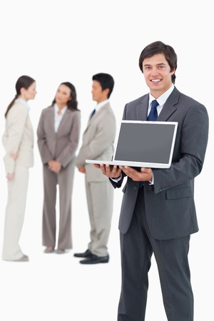 Smiling salesman showing laptop screen with team behind him against a white background photo