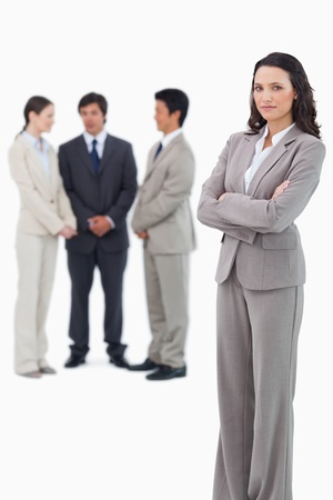 Serious saleswoman with arms crossed and team behind her against a white background photo