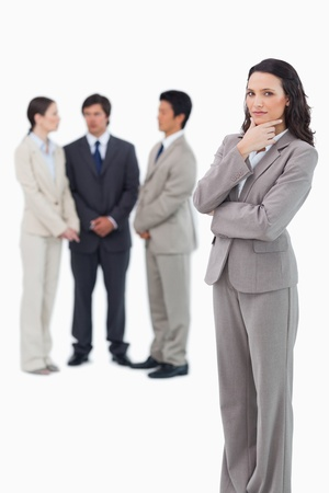 thinkers: Thinking saleswoman with team behind her against a white background Stock Photo