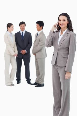 Smiling saleswoman on her cellphone with team behind her against a white background photo