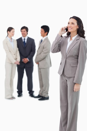 Saleswoman on the cellphone with team behind her against a white background photo