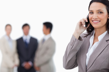 Smiling saleswoman on mobile phone with colleagues behind her against a white background photo