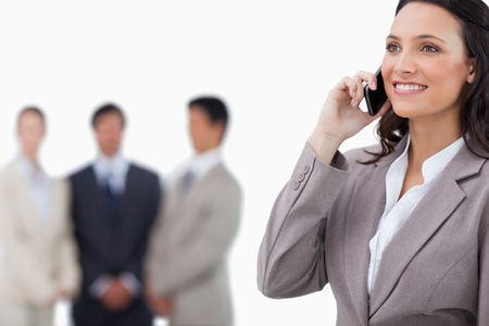Smiling saleswoman on her mobile phone with team behind her against a white background Stock Photo - 13615812
