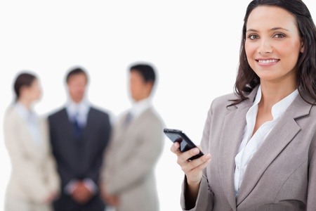 Smiling saleswoman holding cellphone with team behind her against a white background photo