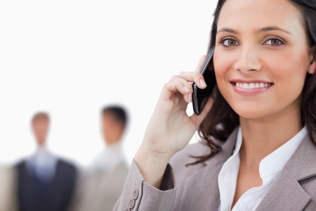 Smiling saleswoman talking on the phone against a white background photo