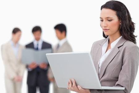 Saleswoman with notebook and colleagues behind her against a white background photo